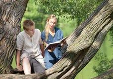 Individuo y muchacha jovenes con los libros de texto en el banco del lago Fotos de archivo