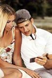Individuo y muchacha lindos que usa el smartphone para la diversión Fotos de archivo libres de regalías