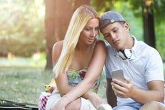 Individuo y muchacha lindos que usa smartphone Foto de archivo