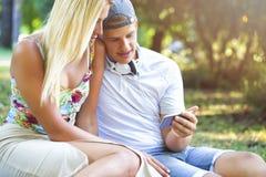 Individuo y muchacha que usa el smartphone para la diversión Imágenes de archivo libres de regalías