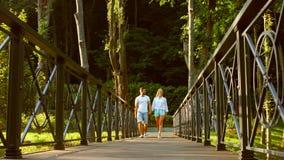 Individuo y una muchacha que camina en un puente en el parque metrajes