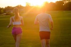 Individuo y una muchacha que corre en el parque Fotos de archivo
