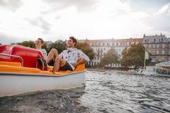 Individuos adolescentes que disfrutan de canotaje en el lago Foto de archivo libre de regalías