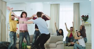 Individuos atractivos y señoras étnicos multi de los amigos que miran en la TV un partido de fútbol ellos que celebran la victori