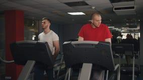 Individuos de la aptitud que corren en la rueda de ardilla en el gimnasio Gente apta de los j?venes que corre en la rueda de ardi almacen de video