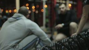 Individuos jovenes Defocused que tienen resto después del entrenamiento en el gimnasio, el hablar masculino de los amigos metrajes