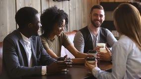 Individuos jovenes diversos que pasan el tiempo junto en café de consumición del café almacen de metraje de vídeo