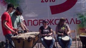 Individuos jovenes elegantes, hermosos, hombres barbudos que colocan el juego en el cosaco, tambores militares, tulumbas, junto c almacen de video