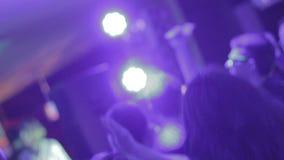 Individuos jovenes que se divierten, moviéndose a la música, disfrutando de ocio en el club almacen de video