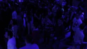 Individuos jovenes que se relajan, divirtiéndose, moviéndose a la música en sala de baile almacen de video