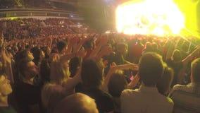 Individuos que agitan las manos simultáneamente en el concierto Efectos luminosos asombrosos sobre etapa almacen de video