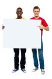 Individuos sonrientes con la tarjeta blanca del anuncio foto de archivo