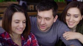 Individuos y muchachas en un primer del café Una morenita hermosa está sosteniendo un smartphone en sus manos, y la está mostrand almacen de video