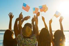 Individuos y muchachas que agitan banderas americanas Imagen de archivo libre de regalías