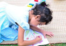 Indo para trás à escola, ao desenho da menina e à pintura sobre a grama verde Fotografia de Stock Royalty Free