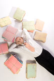 Indolent executive and papers. A man wearing office attire lying back on a white floor with his hands behind his head. Tied up stacks of paper documents strewn Royalty Free Stock Photo