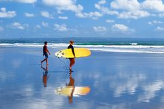 Indonésia, ilha de Bali, Kuta, praia - 10 de outubro de 2017: Surfistas com uma prancha que andam ao longo da praia fotografia de stock
