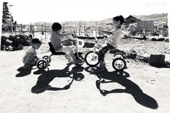 INDONESIA, BALI - AUGUST 2014: A group of unidentified children is playing on their bike. Children from undeveloped countries live stock images