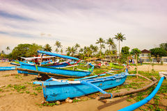 On the coast of the boats. Indonesia Bali island Kuta.Some blue boats stopped at the shore Stock Image