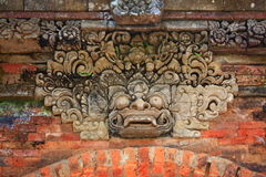 Indonesia, Bali: Sculpture of Kala. Stone sculpture of head's kala; traditionally represented in the top of the front door; a protective image against the Royalty Free Stock Photography