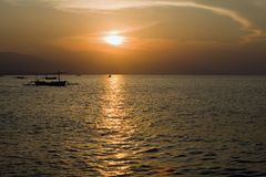 Indonesia. Bali. A sunset over ocean and a boat si Stock Photos