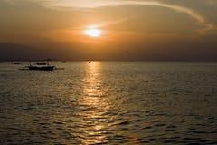 Indonesia. Bali. Una puesta del sol sobre el océano y un barco si Fotos de archivo