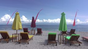 Empty Sunbeds and Umbrellas on the Beach. Fast Motion. Indonesia. Empty beach. The clouds flew quickly and cast a shadow over the sun loungers and sun umbrellas stock video