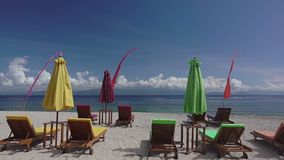Empty sunbeds and umbrellas on the beach. Slow Motion. Indonesia. Empty beach. Sun loungers and sun umbrellas. A volcano in the clouds on the horizon. Slow stock video
