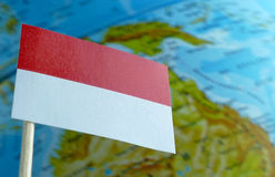 Indonesia flag with a globe map as a background. Macro royalty free stock image