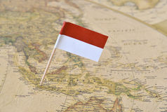 Indonesia flag pin on map. Indonesia paper flag pin on an ancient map stock photography