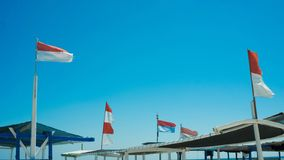Indonesia flag on transporation boat in sea with blue sky and wave stock images
