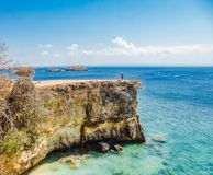 Indonesia - The girl and the Pink Beach Cliff. A girl standing on a dramatic cliff at the Pink Beach on the island of Lombok in Indonesia next to Bali stock photo