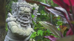 Indonesia god statue on tropical plant background in Bali temple, Indonesia. Traditional indonesian hindu symbol. Indonesia god statue on tropical plants stock footage