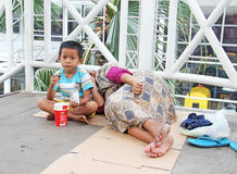 Indonesia, Jakarta. May 18, 2014. Woman with  child begging Royalty Free Stock Photography