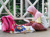Indonesia, Jakarta. May 18, 2014. Woman with  child begging Stock Photos