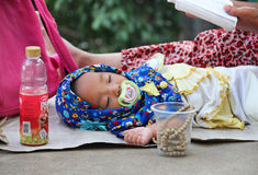 Indonesia, Jakarta. May 18, 2014. Woman with  child begging Royalty Free Stock Photo