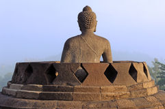 Indonesia, Java, Borobudur: Sunrise. Indonesia, java, Borobudur: a beautifull stone seat buddha in meditation facing to the  sunrise at the most famous asiatic Royalty Free Stock Photography