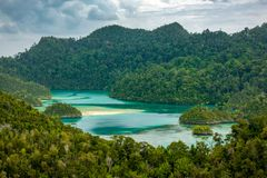 Tropical Lagoon in Cloudy Weather. Indonesia. Lagoon with emerald water surrounded by rocky islands. Wild jungle. Overcast. High point shooting Stock Images