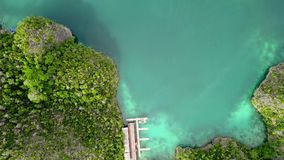 Boat Approaches the Pier and the Tropical Islands. Aerial View. Indonesia. Lots of small tropical islands and azure water. The boat approaches the pier. Aerial stock footage