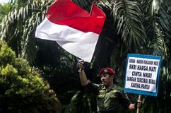 INDONESIA NATIONALISM SENTIMENT. Army Cpl. Partika Soebagyo waive Indonesian Flag at a self hosted loyalty action at Solo, Java, Indonesia. Indonesia use Stock Images