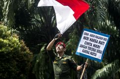 INDONESIA NATIONALISM SENTIMENT. Army Cpl. Partika Soebagyo wave Indonesian Flag at a self hosted loyalty action at Solo, Java, Indonesia. Indonesia use Stock Image