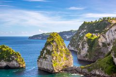 Shore of the Ocean and Huts on the Rocks. Indonesia. The ocean shore of a rocky island. A few huts on top of a cliff among the rainforest Stock Photography