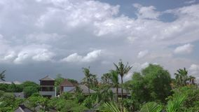 Clouds over roofs and tropical trees. Fast motion. Indonesia. A small village in a dense tropical vegetation. View of the roofs and clouds. Windy weather. Fast stock video