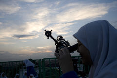 INDONESIA STUDENT ASTRONOMY CLUB. A student, member of a school-based astronomy club, is seeing through a telescope to view sunset in Sukoharjo, Java, Indonesia Stock Images