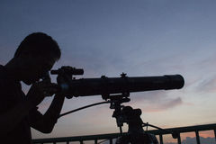 INDONESIA STUDENT ASTRONOMY CLUB. A student, member of a school-based astronomy club, is seeing through a telescope to view sunset in Sukoharjo, Java, Indonesia stock image