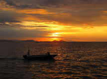 Indonesia Sunset 2. Photo of a fisherman coming home from a busy day against a beautiful red sunset in the Komodo Islands, Indonesia Royalty Free Stock Photo