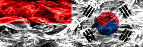 Indonesia vs South Korea smoke flags placed side by side. Thick royalty free stock photography