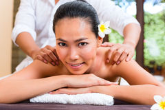Indonesian Asian woman in wellness beauty day spa. Indonesian Asian women in wellness beauty day spa having aroma therapy massage with essential oil, looking Royalty Free Stock Photo