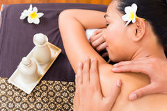 Indonesian Asian woman at wellness spa massage. Masseur giving Indonesian Asian women a aroma therapy massage with essential oil in a beauty wellness spa Royalty Free Stock Image