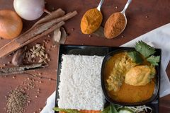 Chicken curry with vegetable, herb and spices powder on a wooden table and white napkin stock photo